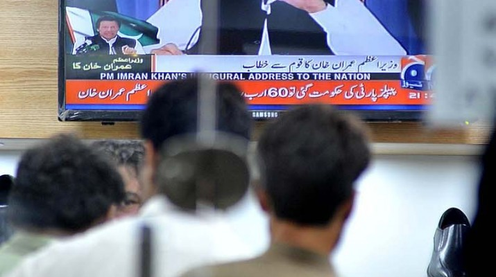 APP57-19 ISLAMABAD: August 19 – People listening the Prime Minister Imran Khan address to nation on television at local shop. APP photo by Irshad Sheikh